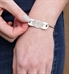 Woman showing the back of the silver tone stainless medical ID tag on the slip-on SmartFit Medical ID Bracelet with SmartBead