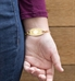 Gold gardenia ID tag attached to Cassie bracelet shown on wrist