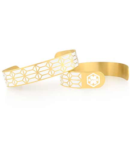 Low profile ladies med ID cuff in yellow tone metal and white inlaid paint features a modern linear pattern.