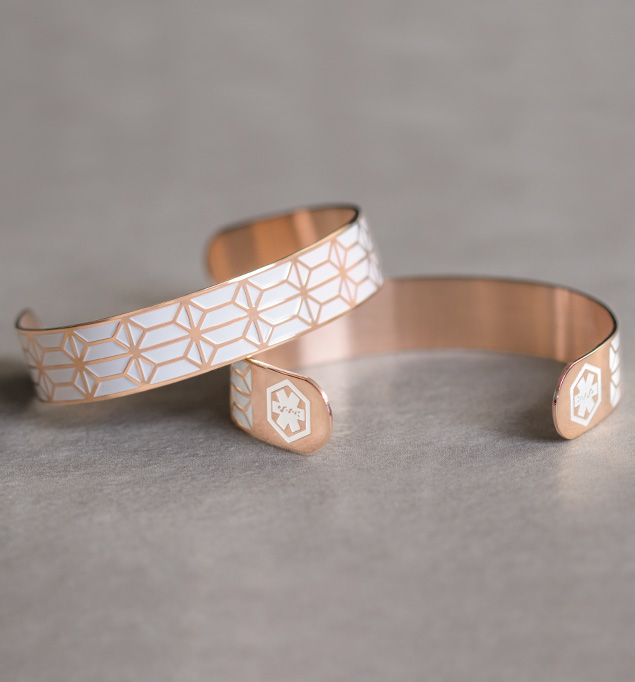 Front and back of rose tone stainless Claudia Medical ID Cuff. Geometric pattern on white background. White caduceus each end