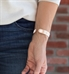 Woman wearing rose tone stainless Claudia Medical ID Cuff. Geometric pattern against white background. White caduceus on ends