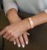 Woman showing the front of rose gold medical ID cuff with white medical symbol