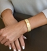 Woman wearing gold tone medical ID cuff with decorative pattern and white medical caduceus symbol