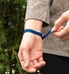 Woman showing the mesh chain with slip-through magnetic closure on the blue-tone stainless Urban Medical Alert