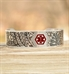 Custom engraved silver metal medical ID cuff with red medical symbol and tropical pattern on wood.