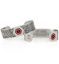 Custom engraved silver metal medical ID cuffs with red medical symbol and tropical pattern.