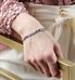 Woman wearing medical alert bracelet with flat pastel beads