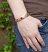 Man wearing Intrepid Medical ID Bracelet. Front of man's rose tone stainless steel link bracelet with red caduceus
