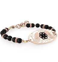 Nora bracelet made of black beads with rose gold accents attached to rose tone guardian angel medical ID tag