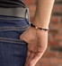 Woman showing back of rose gold linked medical ID bracelet with black accents