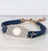 Rose gold and blue adjustable medical ID bracelet on shiplap