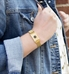 Woman wearing gold tone stainless steel medical alert bracelet with mesh band