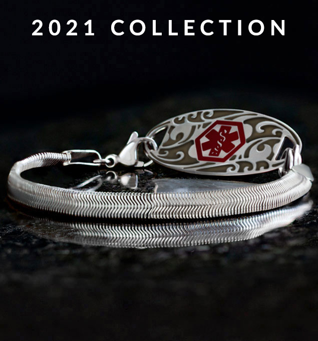 Low angle shot of silver herringbone medical ID bracelet with silver filigree design medical ID tag with red medical caduceus symbol on black stone.