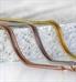 Herringbone medical ID bracelet strands in rose gold, silver, and gold draped over stone slab.