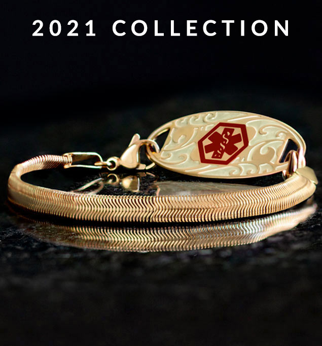 Low angle shot of gold herringbone medical ID bracelet with gold filigree design medical ID tag with red medical caduceus symbol on black stone.