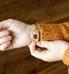 Woman wearing gold herringbone medical ID bracelet with gold filigree design medical ID tag.