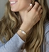Smiling woman wearing linked bracelet with silver and gold alternating heart links