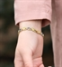 Woman showing the back of gold and silver medical ID bracelet with heart links