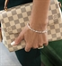 Woman wearing Cantata Medical ID Bracelet showing front view of 3 shapes of cubic zirconia. Carrying fashion purse