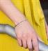 Woman in yellow dress wearing silver tone t-link medical ID bracelet