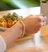 Woman wearing gold tone t-link medical ID bracelet