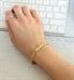 Woman using keyboard wearing gold tone t-link medical ID bracelet