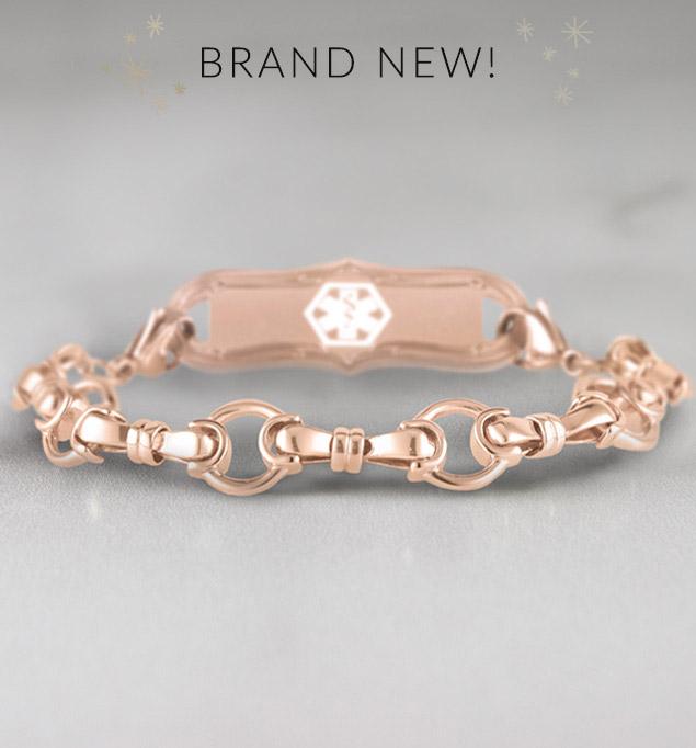 Rose gold bridle chain medical alert bracelet with decorative alert tag on marble background