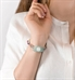 Woman wearing white shirt and turquoise decorative medical alert tag with white caduceus symbol
