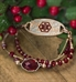 Multi-faceted, gold bezel-set ruby red center stone accented with Gold and Rose gold elements interchangeable bracelet with Christmas holly
