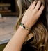 Woman with hand in hair wearing emerald and rose gold beaded medical ID bracelet