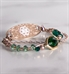 Rose gold and emerald green medical ID bracelet with large green center stone on marble