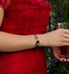 Woman in red dress wearing rose gold and emerald beaded medical ID bracelet