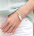 Woman wearing the La Petite White Caduceus Medical ID Tag on the Opal Medical ID Bracelet in Sterling Silver with opal links