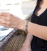 """Woman outside wearing the Antique Gate Medical ID Bracelet chain of stainless black-filled scrolled pattern 3/4"""" x 1/2"""" links"""