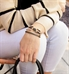Woman wearing Love Song Med ID Bundle with black crystals, gold accents, and black with gold leather bracelet