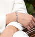 Woman in white blazer wearing silver flat curb chain medical alert bracelet