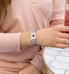 Woman wearing silver mesh medical alert bracelet with floral design and red medical caduceus symbol