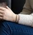 Woman wearing silver herringbone medical ID bracelet and holding drink.