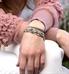 Woman wearing silver herringbone medical alert bracelet with gray beaded medical ID bracelet