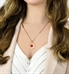 Woman wearing rose gold medical alert pendant necklace with red medical caduceus symbol