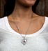 Woman wearing stainless Close To My Heart Med ID Necklace. Asymmetrical heart, textural detail, red caduceus. Oval link chain