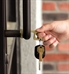 Woman using CleanTouch Keychain to pull open a door