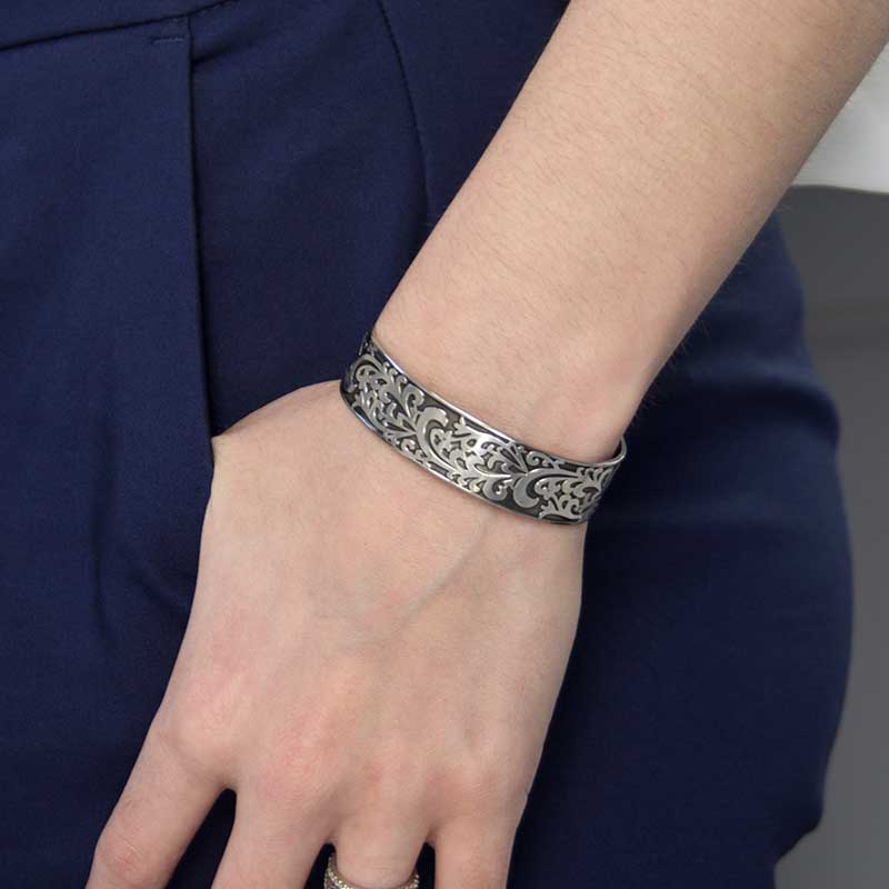 Woman wearing Filigree Medical Alert Cuff. Silver tone stainless cuff, intricately scrolled design with dark patina inlay