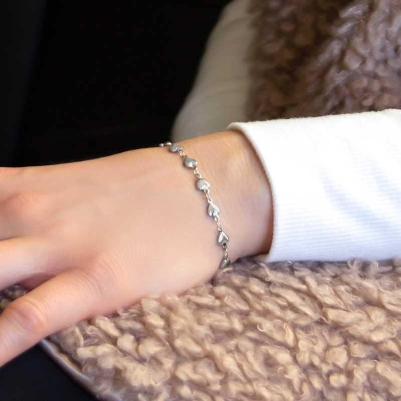 Woman wearing silver medical alert chain with tiny heart links in stainless steel