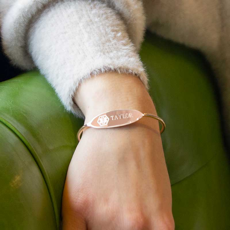 Woman sitting on green chair wearing thin rose gold tone cuff with white medical symbol