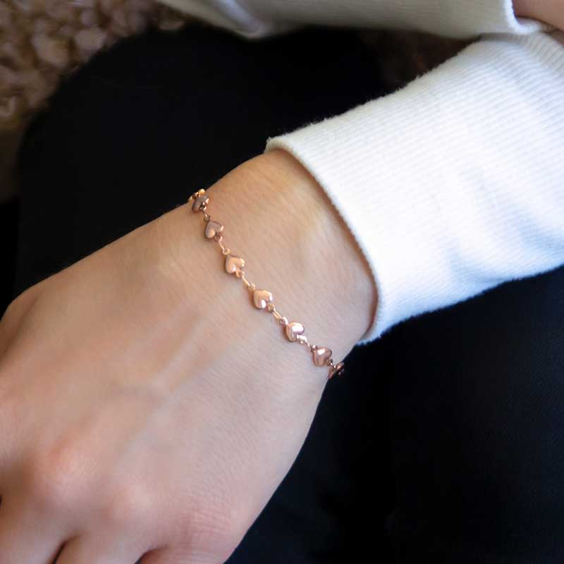 Woman wearing rose gold chain medical ID bracelet with tiny heart links