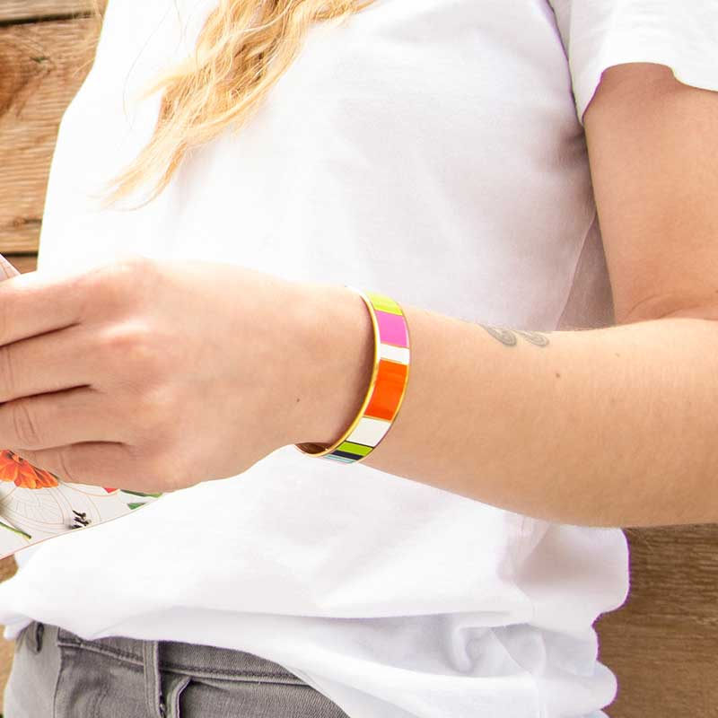 Woman wearing Key West Medical ID Cuff. Orange pink white magenta lime navy and teal color blocks,yellow gold background