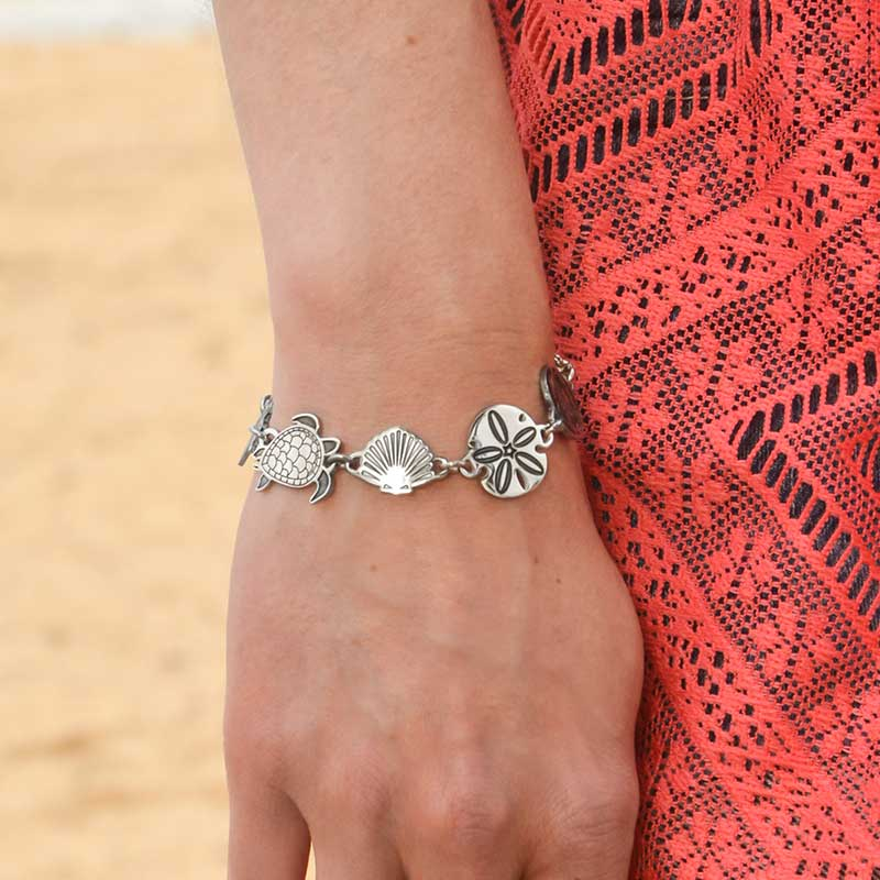 Woman wearing the silver tone stainless Sea Life Medical ID Bracelet with the sea turtle, shell and sand dollar links visible