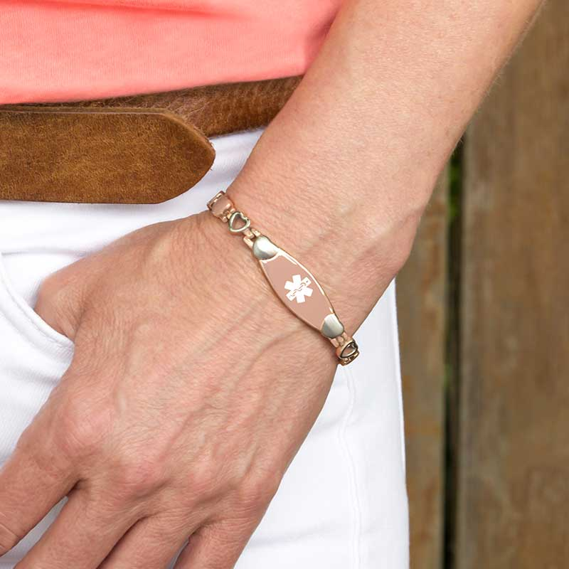Woman wearing Rose Tone Love Links Medical ID Bracelet, plated stainless alternating rose and silver hearts, white caduceus