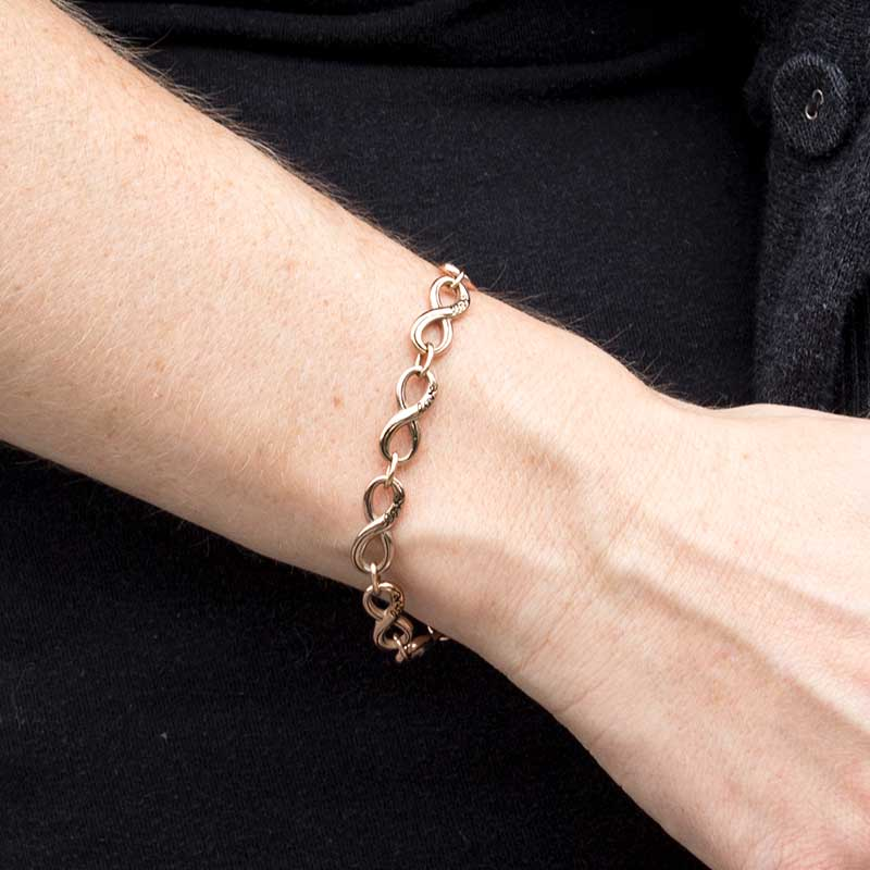 Interlocking rose gold tone infinite symbols make a single chain that attaches to a medical ID tag.